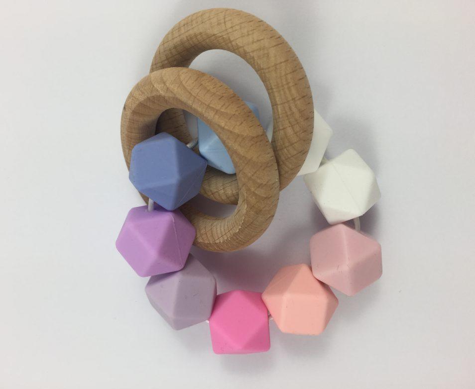 Joli petit hochet en silicone et deux anneaux de dentition en bois naturel sans traitement de type Montessori.